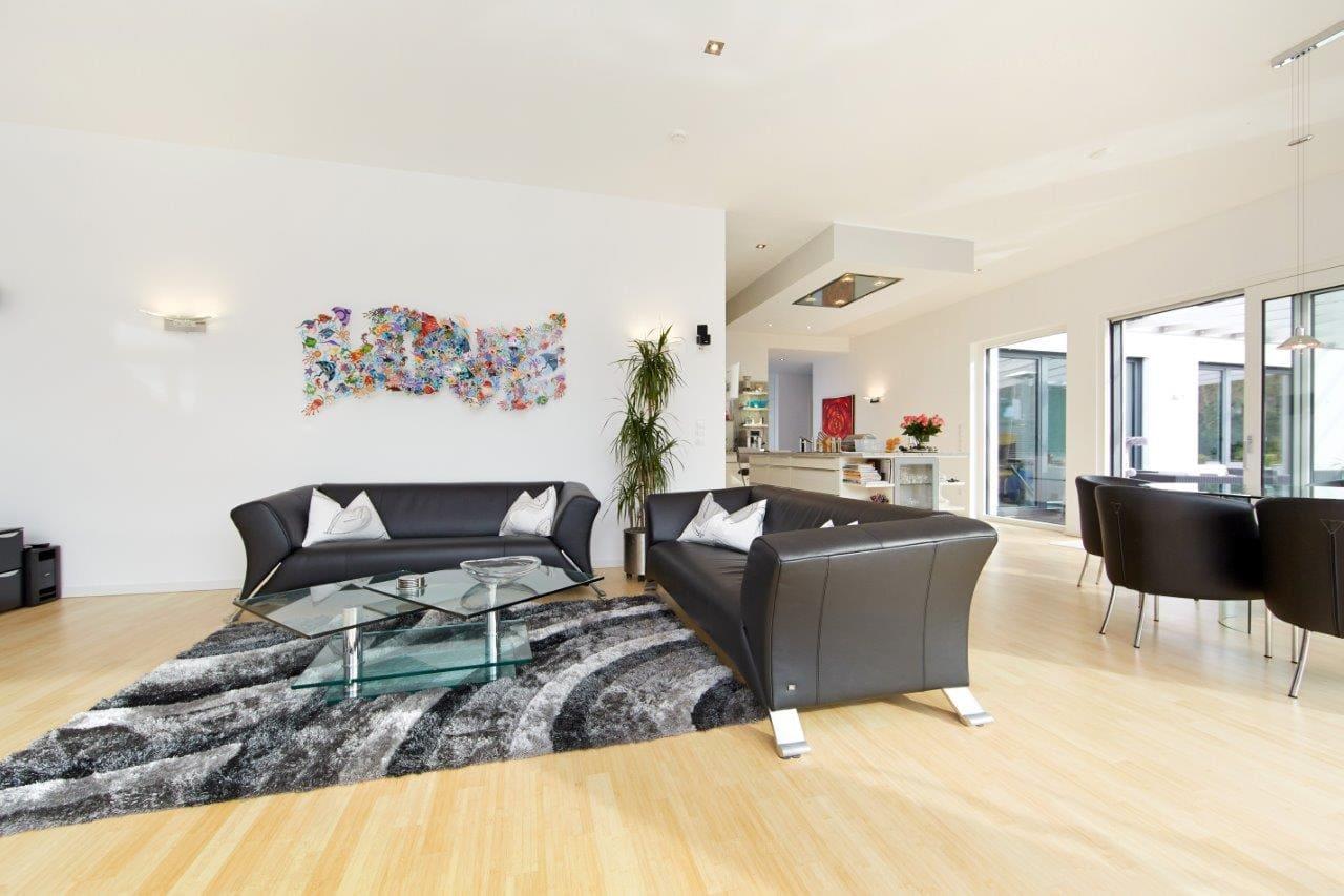 Wohnzimmer modern mit offener Küche & Essbereich - Inneneinrichtung Ideen Fertighaus Bungalow Toulouse von GUSSEK HAUS - HausbauDirekt.de
