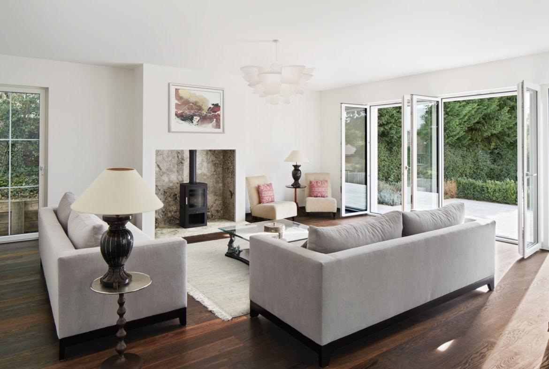 Wohnzimmer mit Kamin & bodentiefen Fenstern - Haus Design Inneneinrichtung Luxus Villa ATHERTON von Baufritz - HausbauDirekt.de