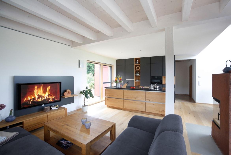 Offenes Wohnzimmer mit Kamin - Haus Design innen modern Ideen Inneneinrichtung Baufritz ÖKOHAUS SCHELLENBERG - HausbauDirekt.de