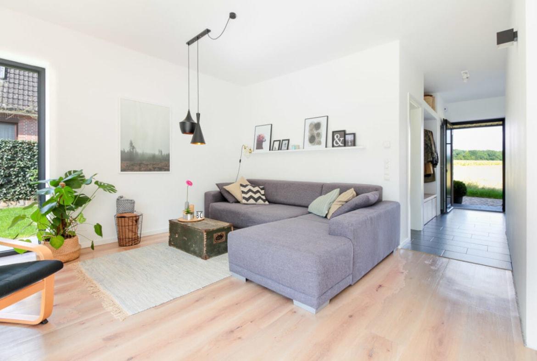 Wohnzimmer mit Ecksofa - Inneneinrichtung Haus Design Ideen innen Massivhaus Vario-Haus 160 von ECO System HAUS - HausbauDirekt.de