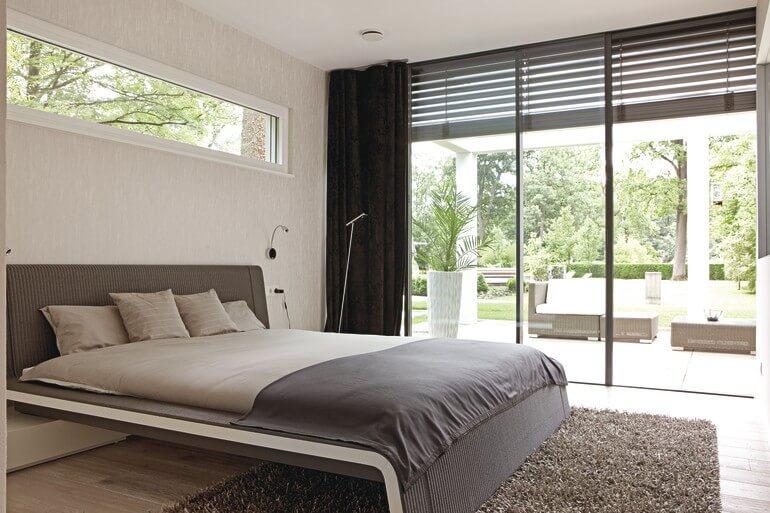 Bungalow Inneneinrichtung Schlafzimmer modern offen mit großer Glas Fassade - Haus barrierefrei bauen Design Ideen innen & aussen WeberHaus Winkelbungalow ebenLeben - HausbauDirekt.de