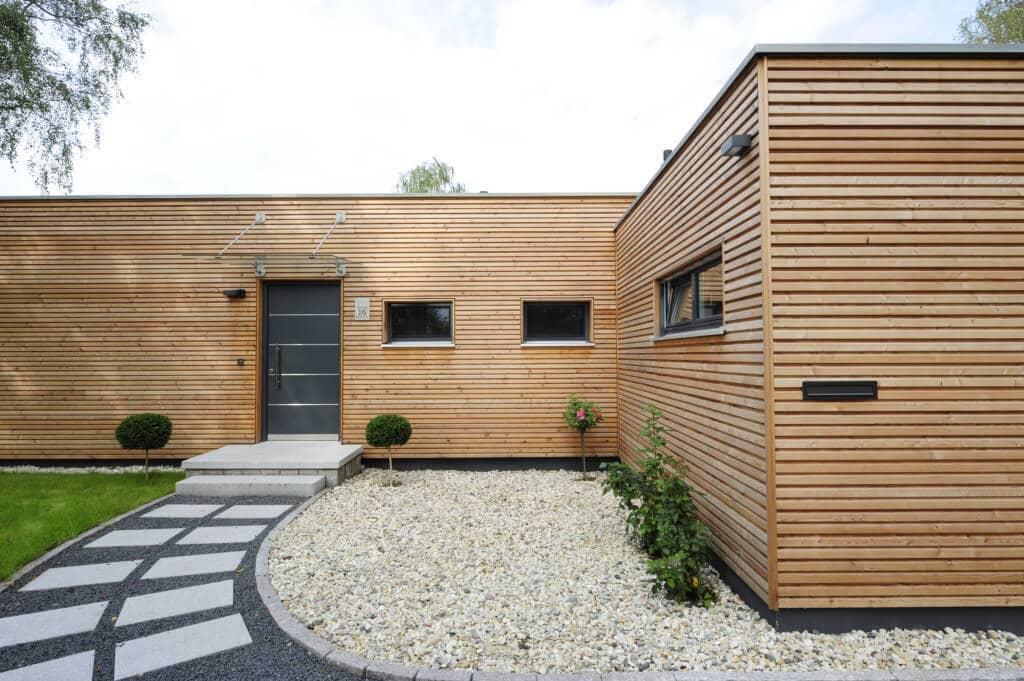 Moderner Bungalow mit Flachdach & Holz Fassade bauen, Hauseingang - Haus Design Ideen Fertighaus Bungalow von Baufritz - HausbauDirekt.de